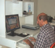 Male client sitting at desk, practicing computer skills.