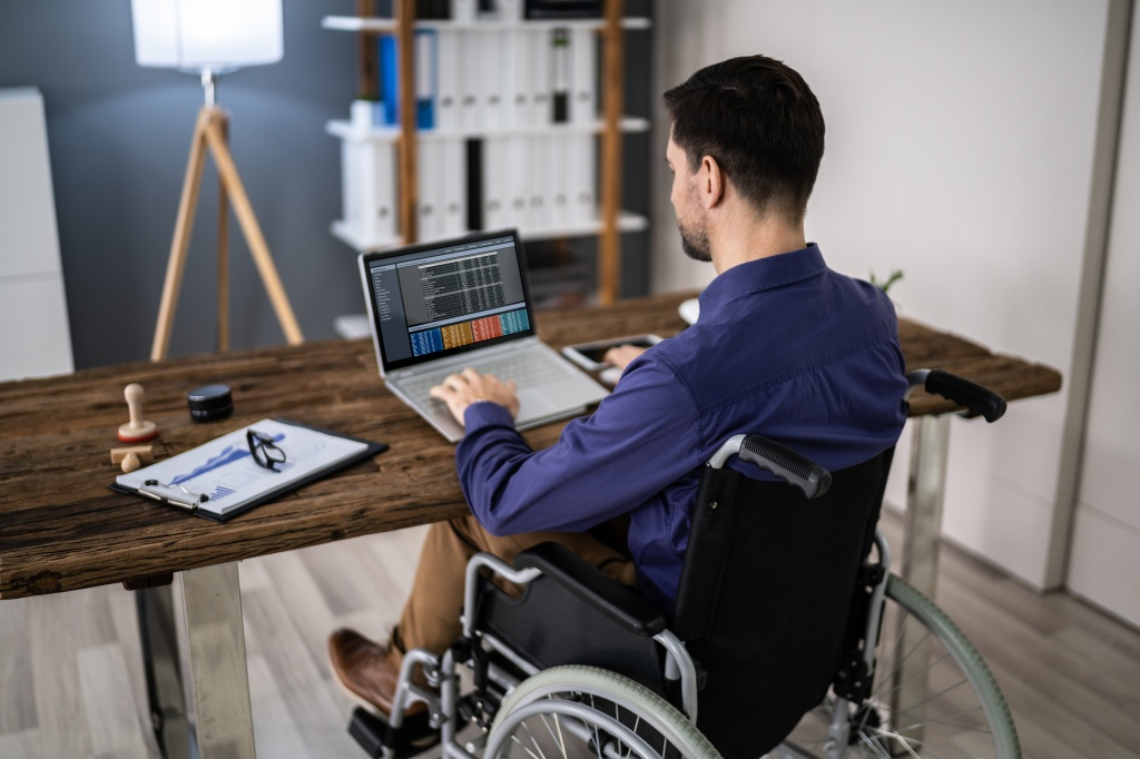 Young man sitting in wheelchair, using a notebook computer at a desk.