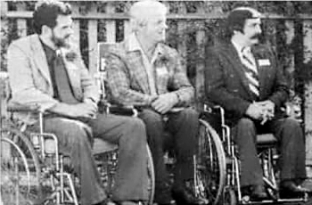 Black and white photo in 1976, with 3 men in wheelchairs. Darrell McDaniel, Lou Nau and Bob Campbell. Co-Founders.