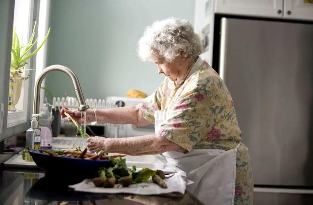 Senior lady wearing an apron, washing vegetables at kitchen sink.