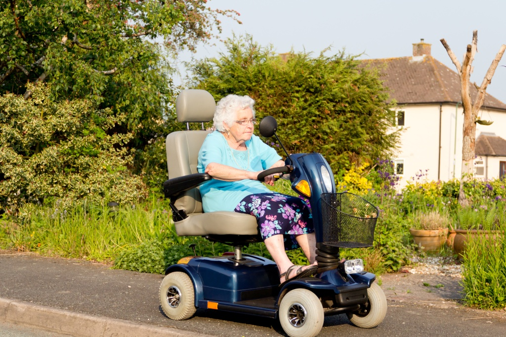 Senior lady with disability driving a mobility scooter on sidewalk by country style house and greenery.